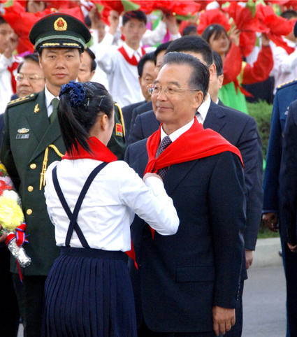 A member of the Korean Children's Union confers honorary membership on Wen Jiabao (Photo: Korean Central News Agency)