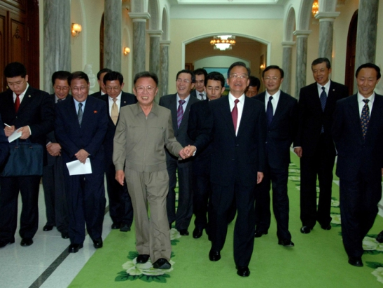 Kim Jong-il and Wen Jaibao clasp hands following a dinner at the Paekhwawon Guest House.  At left is an unidentified aide to Premier Wen, Jang Song-thaek and Kang Sok-ju. (Photo: Korean Central News Agency)