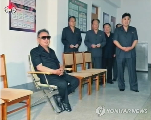Kim Jong Un (R) visits the 11 May Factory with his father, late leader Kim Jong Il, in July 2011 (Photo: KCNA-Yonhap).
