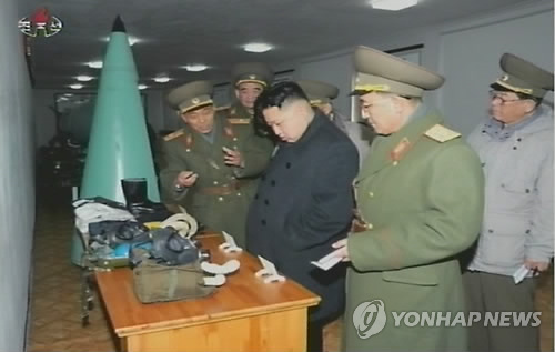 Kim Jong Un (3rd R) looks at training equipments during his visit to the KPA Strategic Rocket Force Command in the suburbs of Pyongyang.  Also in attendance is Gen. Pak Jae Gyong (R) (Photo: KCNA-Yonhap)