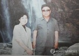 A woman identified as Ri U'n-sil (L), but believed to be Ko Yong Hui, Kim Jong Un's mother, poses for a commemorative photograph with Kim Jong Il (Photo: Mainichi Shimbun-Yonhap)