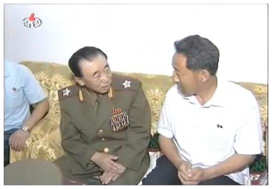 VMar Hyon Chol Hae talks with a Changjon Street resident while visiting the man's apartment on 6 July 2012 (Photo: KCNA/KCTV still)