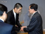 Jang Song Taek (R) shakes hands with Moon Hyung-jin (L) during a ceremony where Jang presented a condolence message and floral wreath to Moon, whose father, Rev. Sun Myung Moon, founder of the Unification Church, died on 3 September 2012 (Photo: KCNA)