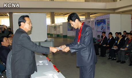 DPRK Vice Premier Kim Yong Jin (L) presents an award to a participant of the 23rd National Software Contest and Exhibition in Pyongyang on 25 October 2012 (Photo: KCNA)