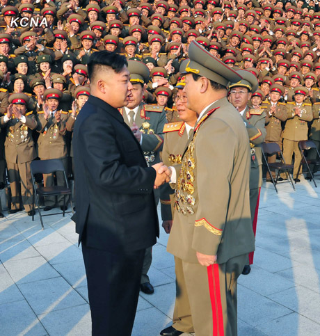 Kim Jong Un (L) shakes hands with Minister of State Security, Gen. Kim Won Hong, during a commemorative photo session with MSS personnel (Photo: KCNA)