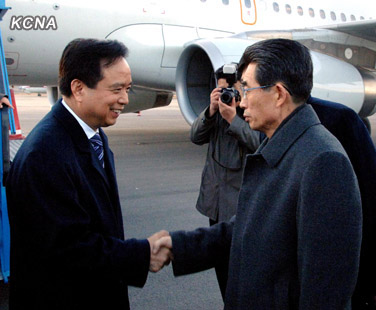 Li Jianguo (L) shakes hands with KWP International Affairs Department Deputy Director Kim Song Nam (R) after arriving at Pyongyang Sunan Airport on 29 November 2012 (Photo: KCNA)