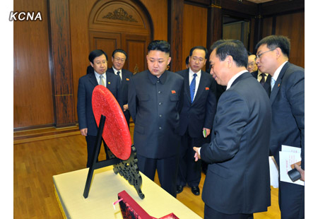 Li Jianguo  explains a gift the CPC delegation presented to Kim Jong Un (Photo: KCNA)