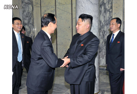 Kim Jong Un (R) shakes hands with Wang Jiarui (L) head of the CPC Central Committee Liaison Department (Photo: KCNA)