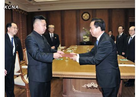 Li Jianguo (R) hands Kim Jong Un (L) a letter from CPC General Secretary Xi Jinping (Photo: KCNA)