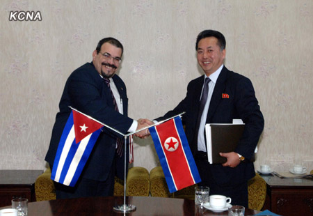 DPRK Minister of Foreign Trade Ri Ryong Nam (R) shakes hands with Cuban Ambassador to the DPRK Germán Hermín Ferras Álvarez (L) at a signing ceremony in Pyongyang on 12 December 2012 (Photo: KCNA)