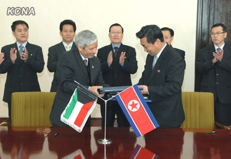 Deputy Director of the Kuwait Fund for Arab Economic Development Hesham Al-Waqayan (L) exchanges copies of cooperation agreement with DPRK Vice Minister of Land and Environment Kim Song Hak (R) during a signing ceremony at the People's Palace of Culture in Pyongyang on 12 December 2012 (Photo: KCNA)