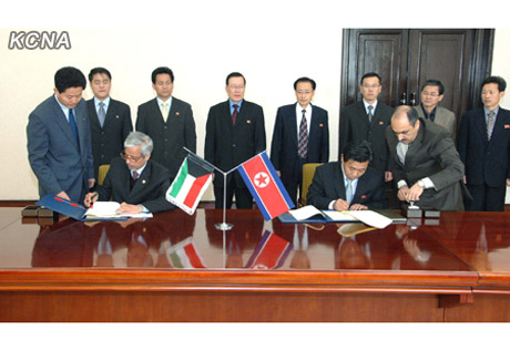 DPRK Vice Minister of Land and Environment Protection Kim Song Hak (R) and Deputy Director of the Kuwait Fund for Arab Economic Development Hesham Al-Waqayan (L) sign a cooperation agreement in Pyongyang on 12 December 2012 (Photo: KCNA)