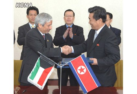 Deputy Director of the Kuwait Fund for Arabic Economic Development Hesham Al-Waqayan (L) shakes hands with DPRK Vice Minister of Land and Environment Protection Kim Song Hak (R) shakes hands after signing a cooperation agreement at the People's Palace of Culture in Pyongyang on 12 December 2012 (Photo: KCNA)