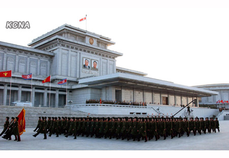 KPA service members march past a platform (review stand) during a memorial and loyalty meeting staged by the military at Ku'msusan on 17 December 2012 (Photo: KCNA)