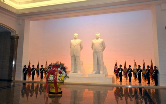 A floral basket from Kim Jong Un sits in front of statues of Kim Il Sung and Kim Jong Il at the Ku'msusan Memorial Palace.  KJU visited Ku'msusan, where the preserved remains of his father and grandfather lie in state, on at midnight on 24 December 2012 in commemoration of the 21st anniversary of Kim Jong Il's assumption of office as KPA Supreme Commander on 24 December 1991.  24 December is also the birthday of Kim Jong Suk, mother of Kim Jong Il (1941-2011) and his sister Kim Kyong Hui (1946--) (Photo: Rodong Sinmun)