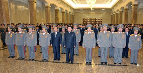 Kim Jong Un (6th L) pays his respects in front of statues of his grandfather Kim Il Sung and his father Kim Jong Il, during a visit to the Ku'msusan Memorial Palace in Pyongyang on 24 December 2012.  In attendance in the front row are: Kim Won Hong (L), Pak To Chun (2nd L), Kim Yong Chun (3rd L) Choe Ryong Hae (4th L), Choe Chun Sik (5th L), Jang Song Taek (4th R), Hyon Yong Chol (3rd R) Kim Kyok Sik (2nd R) and Hyon Chol Hae.  Visibile in the second row are: Kim Kyong Ok (5th L) and Yun Jong Rin (3rd R) (Photo: Rodong Sinmun)