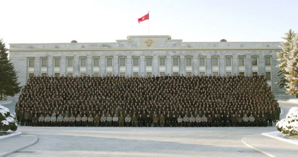 Kim Jong Un (seated, 1st row, 19th L) poses for a commemorative photograph with personnel who contributed to the 12 December 2012 launch of the U'nha-3 rocket and Kwangmyo'ngso'ng-3 satellite in front of the KWP Central Committee #1 Office Building in central Pyongyang (Photo: Rodong Sinmun)
