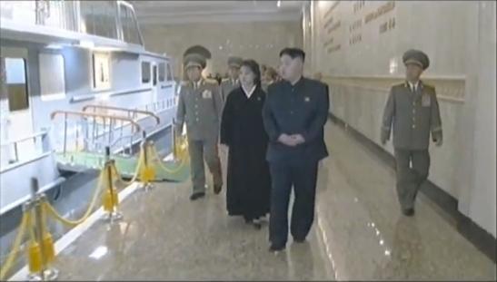 Kim Jong Un (R) and Ri Sol Ju (2nd R) view the display of KJI's boat (Photo: KCTV/KCNA screengrab)