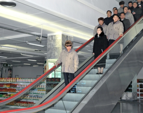 Kim Jong Il (front) at his last reported public appearance at the Kwangbok Market in December 2011.  This was the last image of the late leader when he was alive telecasted in DPRK state media before he died on 17 December 2011 (Photo:  Rodong Sinmun)