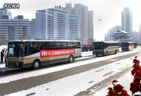 Buses transporting rocket launch personnel ride past  the Pot'ong Gate, at the intersection of Ch'angkwang and Ch'o'llima Streets in central Pyongyang on 4 January 2013 (Photo: KCNA)