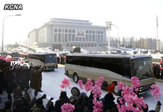 Buses containing participants in the 12 December 2012 launch of the U'nha03 rocket ride past the 25 April House of Culture in Pyongyang on 4 January 2013 (Photo: KCNA)