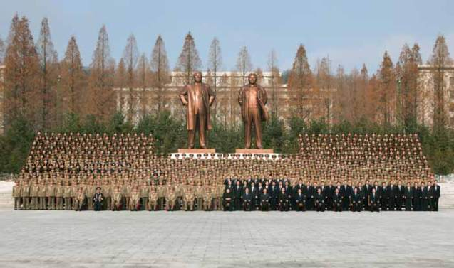 Kim Jong Un poses for a commemorative photograph with participants at a meeting of