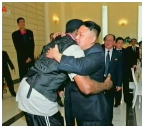 Dennis Rodman (L) embraces Kim Jong Un (R) prior to departing a banquet hosted in the central party complex by the DPRK Olympic Committee.  Seen in the background, L, is DPRK basketball star Ri Myong Hun (a.k.a. Michael Ri) (Photo: KCTV screengrab)