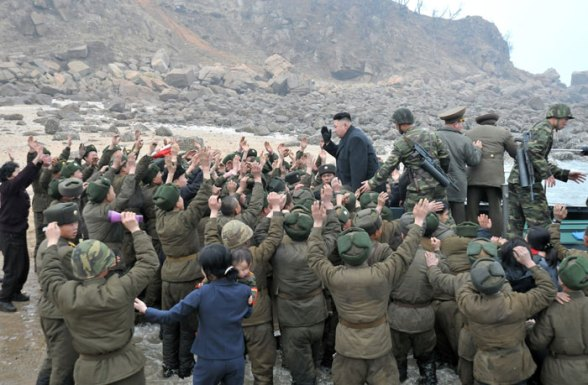 Kim Jong Un disembarks from a transport vessel, greeted by KPA service members and officers, and their family members, on Mu Islet in the West Sea.  Seen behind Kim Jong Un are two close protection escorts carrying automatic rifles and two other executives of KJU's bodyguard staff (Photo: Rodong Sinmun)