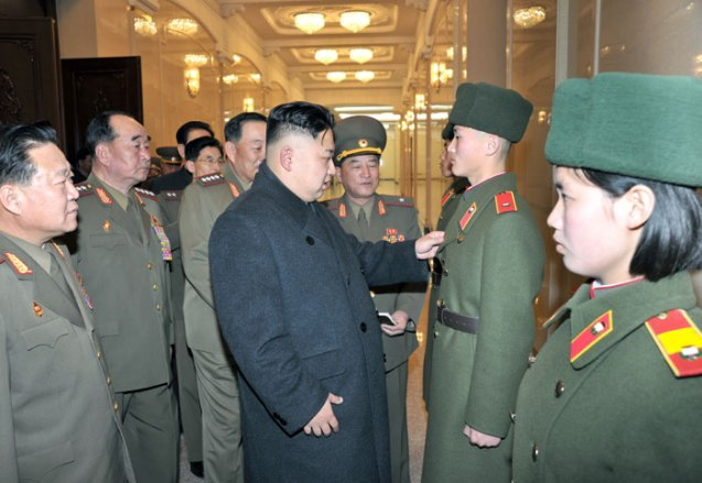 Kim Jong Un (C) inspects a the color of an overcoat, part of the uniform for the student body of the Mangyo'ngdae and Kang Pak Sok Revolutionary Schools in Pyongyang on 24 March 2013.  Also seen in attendance are VMar Choe Ryong Hae (L) and Gen. Kim Kyok Sik (2nd L) (Photo: Rodong Sinmun)
