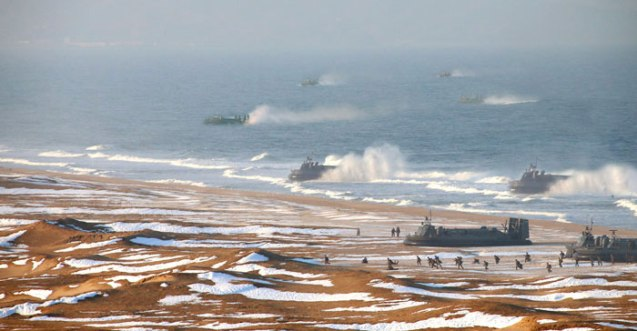 Hovercraft (ACVs) of KPA Navy Combined Unit #597 land on the country's east coast whilst ground forces charge toward simulated targets on the beach (Photo: Rodong Sinmun)