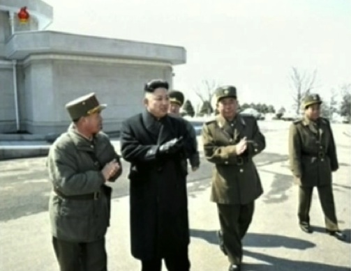 Kim Jong Un (2nd L) greets participants in live fire anti-aircraft exercises prior whilst arriving at a commemorative photo session with the exercises' participants (Photo: KCTV screengrab)