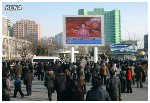 DPRK citizens watch a KCTV anchorwoman read a statement of the KPA Supreme Command on a jumbotron outside Pyongyang Central Railway Station on 26 March 2013 (Photo: KCNA)