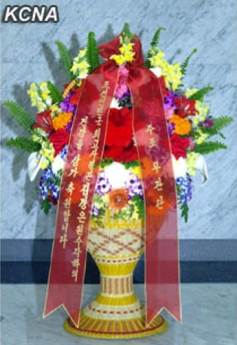 A floral basket delivered by foreign military attaches stationed in the DPRK, sent to Kim Jong Un, to commemorate the 20th anniversary of his father, Kim Jong Il's election as chairman of the National Defense Commission.  The floral basket was delivered by Iranian military attache Hassan Reza Husseini, dean of foreign military attaches in the DPRK, and accepted by Gen. Kim Kyok Sik, Minister of the People's Armed Forces, on 8 April 2013.  (Photo: KCNA)