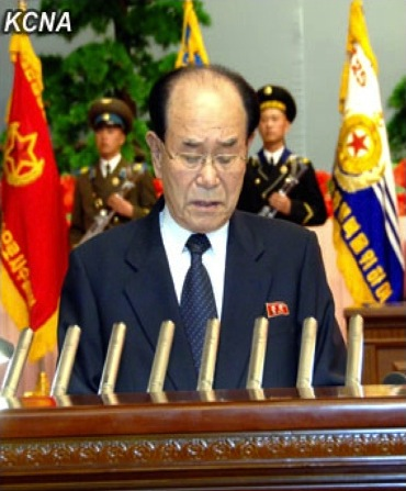Kim Yong Nam, President of the SPA Presidium and Member of the KWP Political Bureau Presidium, reads the report at a national meeting marking Kim Jong Un's election as KWP 1st Secretary and NDC 1st Chairman (Photo: KCNA)