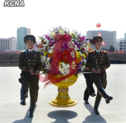 An honor guard delivers a floral basket sent by Kim Jong Un to a ceremony dedicating statues of his grandfather, late DPRK President and founder Kim Il Sung, and his father, late leader Kim Jong Il, at the headquarters of the Ministry of People's Security in Pyongyang on 14 April 2013 (Photo: KCNA)
