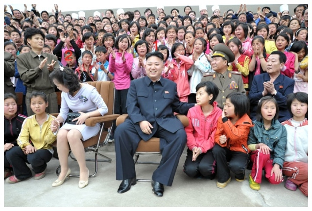 Kim Jong Un (1) and his wife Ri Sol Ju (2) interact with children campers during a commemorative photo session after KJU toured the Mt. Myohyang Children's Camp in North P'yo'ngan Province on 19 May 2013 (Photo: Rodong Sinmun)