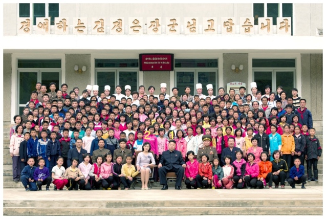Kim Jong Un (1) and his wife Ri Sol Ju (2) pose for a commemorative photograph with campers, employees and officials at Mt. Myohyang Children's Camp on 19 May 2013 (Photo: Rodong Sinmun).