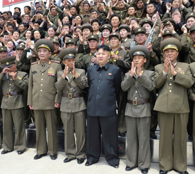 Kim Jong Un (1) stands for a commemorative photograph with the officers, service members and employees of the fishing and boat repair facility subordinate to KPA Unit #639 (Photo: Rodong Sinmun).