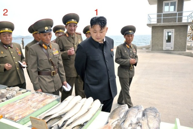 """Kim Jong Un (1) looks at fish caught by the """"supply base"""" of KPA Unit #639.  Also in attendance is Col. Gen. Son Chol Ju (2) (Photo: Rodong Sinmun)."""