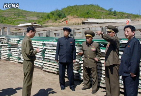 DPRK Premier Pak Pong Ju (1) is briefed about the construction of KPA Breeding Station #621, a facility which will breed grass-fed livestock.  Also in attendance is DPRK Vice Premier and State Planning Commission Chairman Ro Tu Chol (2) (Photo: KCNA).