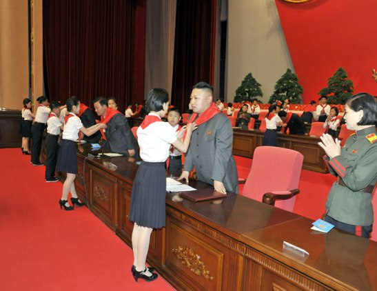 A member of the Korean Children's Union ties a red neckerchief around Kim Jong Un's neck prior to the 7th Congress of the Korean Children's Union in Pyongyang on 6 June 2013 (Photo: Rodong Sinmun).