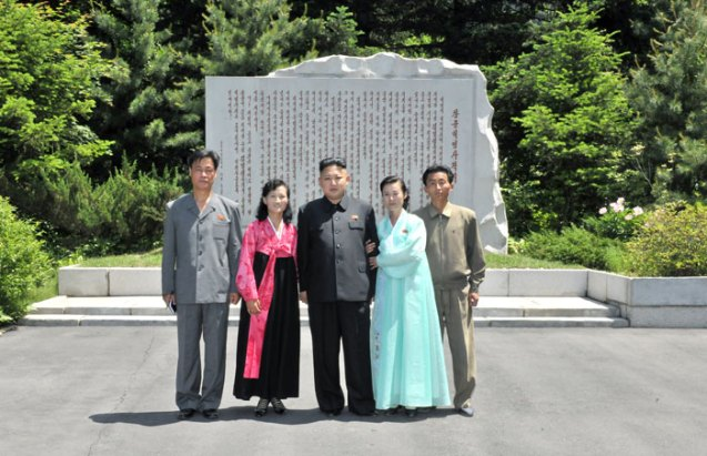 Kim Jong Un (C) poses for a commemorative photograph with museum employees in front of a revolutionary historical marker at Ch'angso'ng Revolutionary Museum (Photo: Rodong Sinmun)