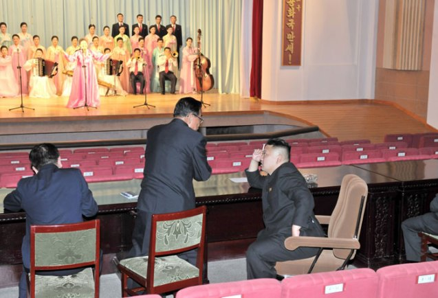 Kim Jong Un (R) smokes a cigarette and talks with a subordinate during a performance by the Ch'angso'ng County art propaganda squad at the county's cultural hall (Photo: Rodong Sinmun).