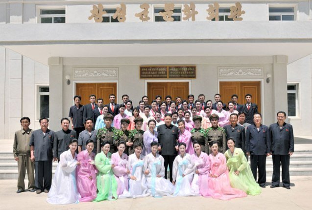 Kim Jong Un poses for a commemorative photographs with members of the Ch'angso'ng County art propaganda squad in front of the county cultural hall (Photo: Rodong Sinmun).