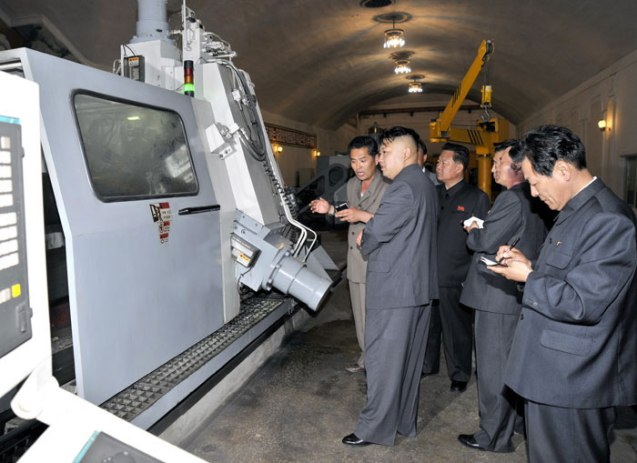Kim Jong Un is briefed about a machine at Kanggye General Tractor Plant (Photo: Rodong Sinmun).