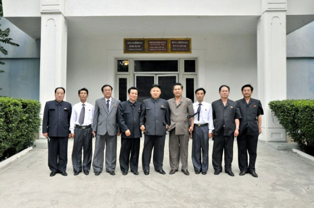 Kim Jong Un (C) poses for a commemorative photograph with personnel and managers of the Kanggye General Tractor Plant (Photo: Rodong Sinmun).