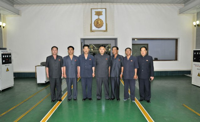 Kim Jong Un (C) poses with officials of the Jangjagang Machine Tools Plant (Photo: Rodong Sinmun).