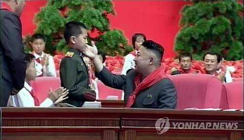 Kim Jong Un attends greets a member of the Korean Children's Union (KCU) during the KCU's 7th Congress held at 25 April House of Culture in Pyongyang on 6 June 2013 (Photo: KCTV-Yonhap)