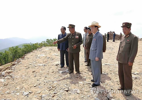 DPRK head of state Kim Yong Nam (2nd R) is briefed about the construction of a ski slope at the construction of Masik Pass Ski Park on 9 June 2013