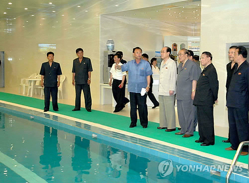 DPRK nominal head of state Kim Yong Nam and other senior DPRK officials view an employees' swimming pool at Pyongyang Essential Foodstuffs Factory (Photo: KCNA-Yonhap).